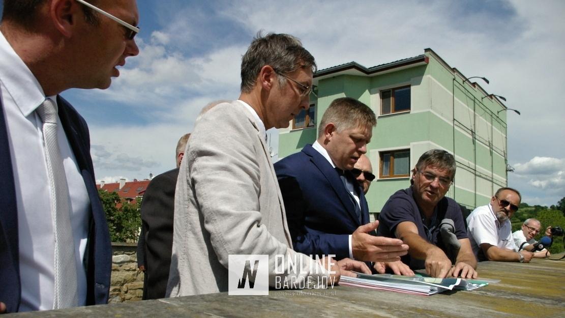 """Vedúci odddelenia výstavby M. Grus (vpravo) ukazuje premiérovi R. Ficovy vizualizácie """"Horného"""" hradu."""